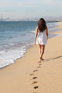 Woman walking on the beach back