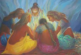 Group of women in diverse bright colors gathered around a fire, seated and bending forward.